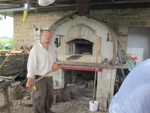Greg Boulos Cooking Pizzas In the Wood Fire Pizza Oven