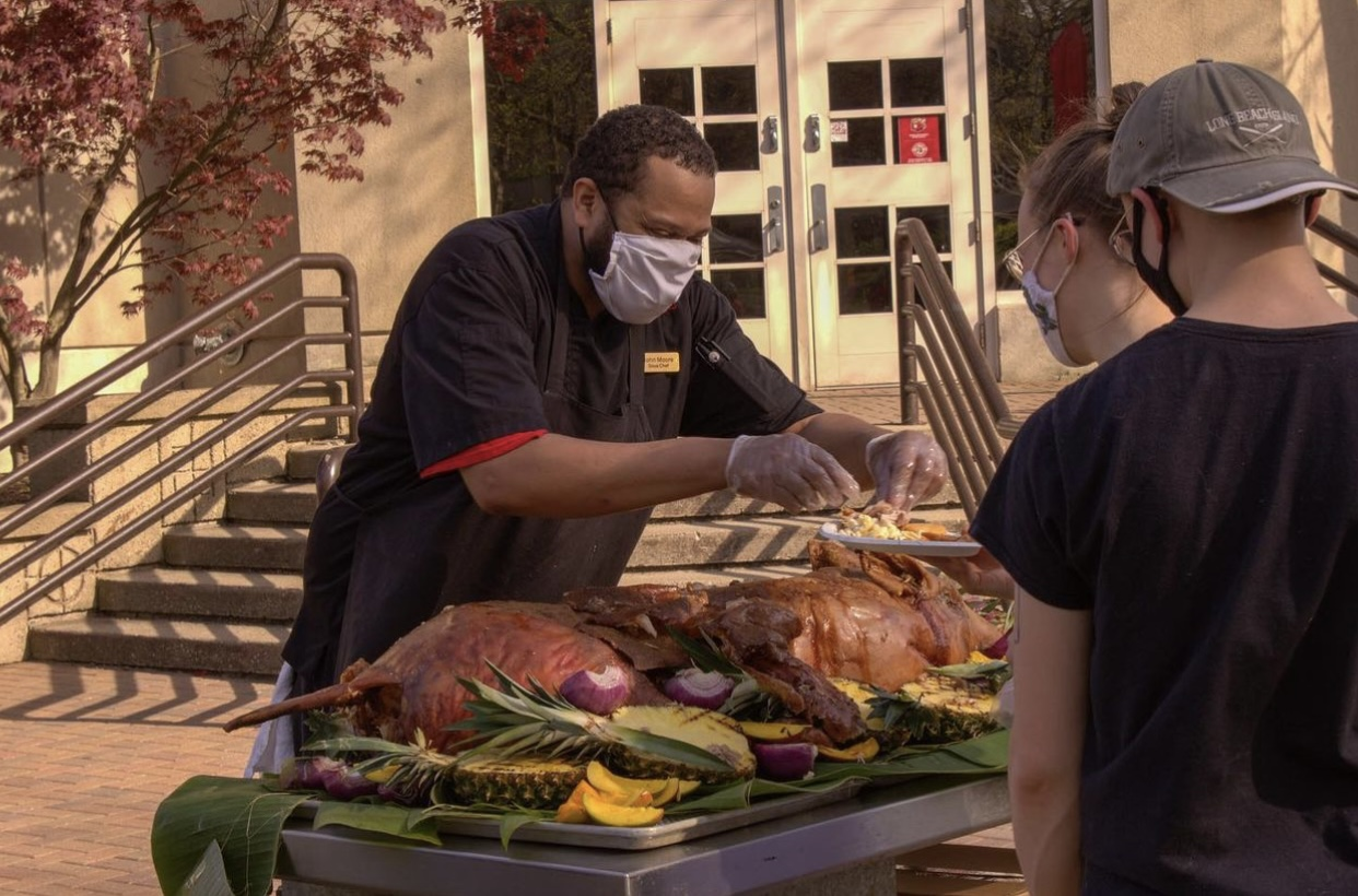 A team members carves ham for students